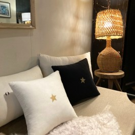 Square black linen cushion with a gold star