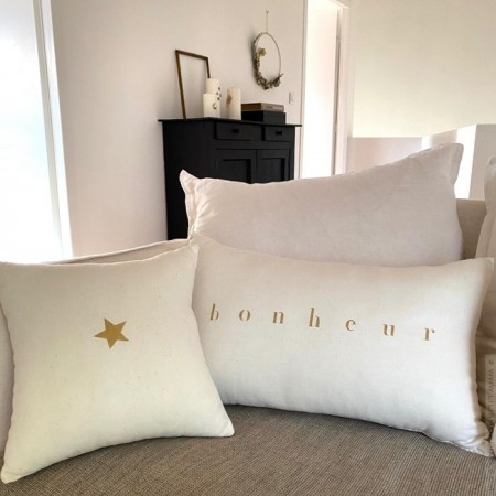 Square old white linen cushion with a gold star