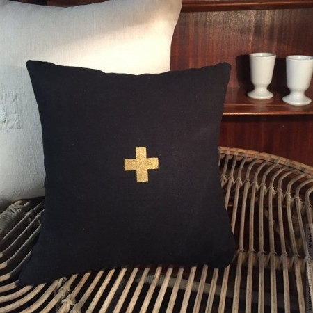 Square black linen cushion with a gold cross
